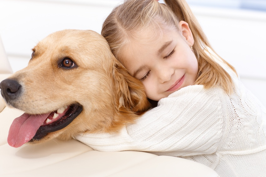 Cute little girl and dog embracing